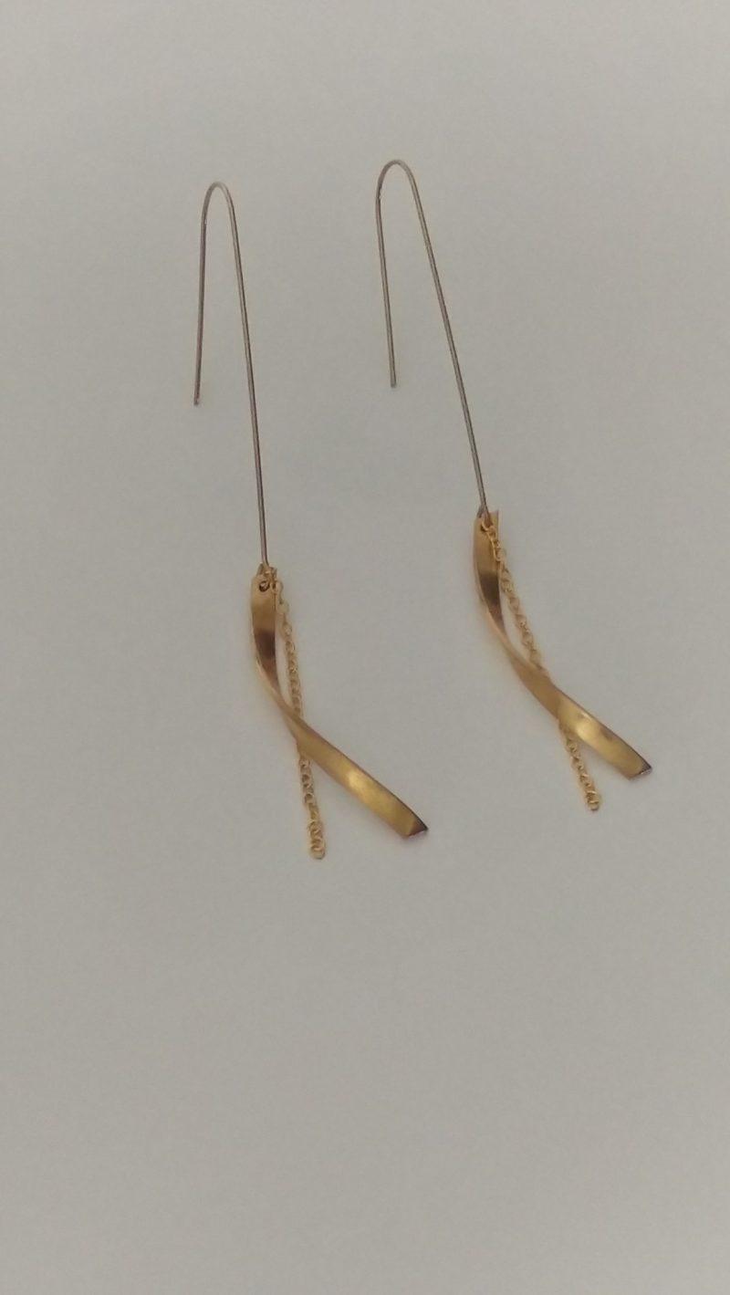 Boucles d'oreilles en laiton aux formes courbées. Elles sont agrémentées d'une fine chaîne en acier inoxydable. Dans un style chic et épuré ces jolis accessoires apporteront une touche d'originalité à votre tenue.