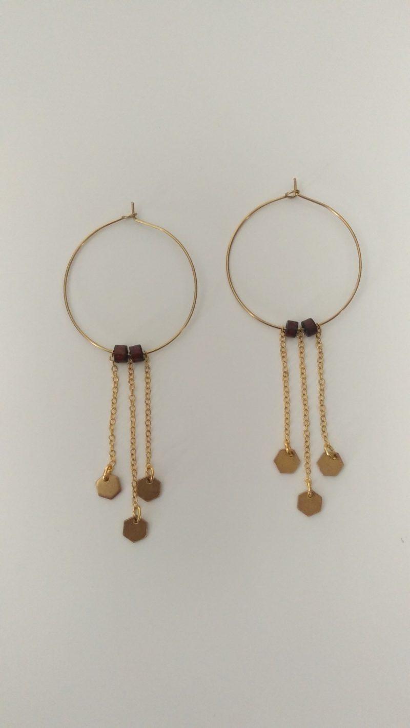 Boucles d'oreilles créoles en laiton. Elles sont agrémentées de fines chaînes et hexagones en laiton brut et de bois.